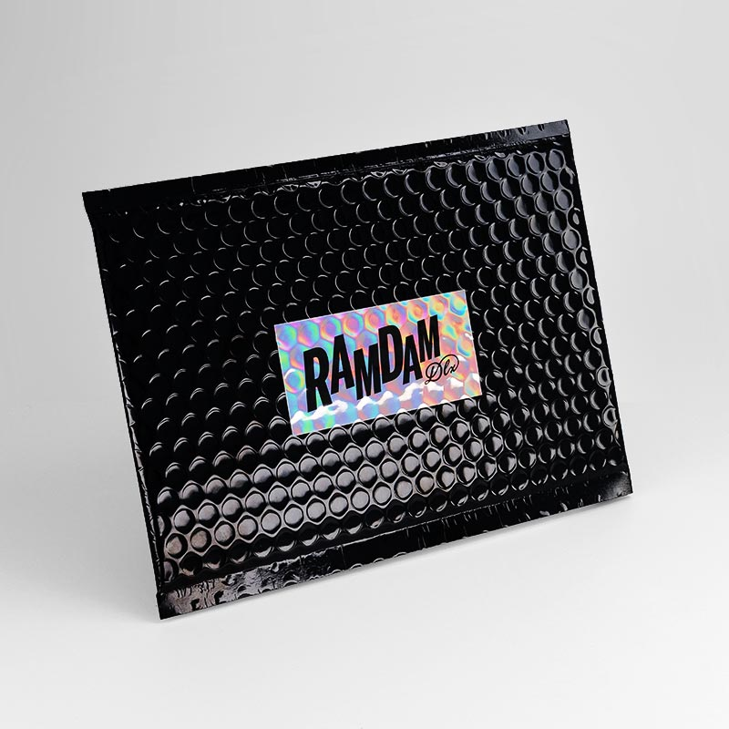 Black metal bubble envelope, Ramdam Dlx logo on holographic rectangle.