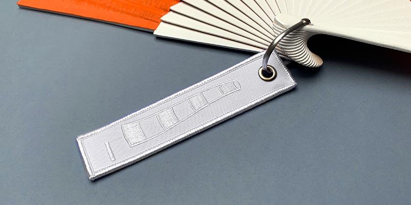 Étiquette brodée blanche, motif manche à air.