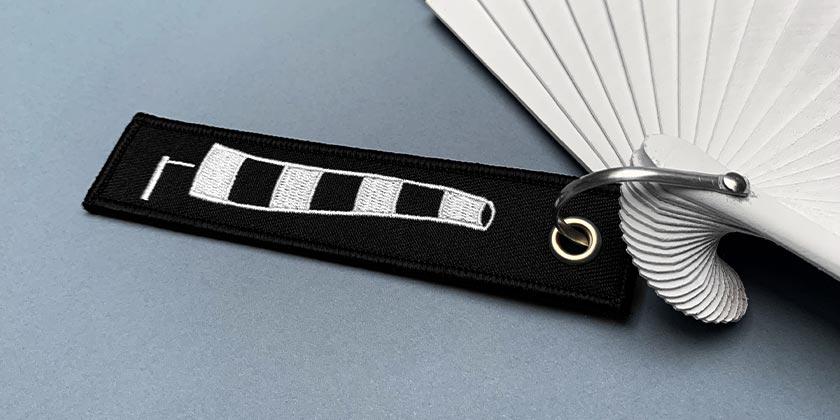 Black and white embroidered tag, windsock graphic.