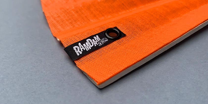 Detail of the black and white woven label with Ramdam Dlx logo
