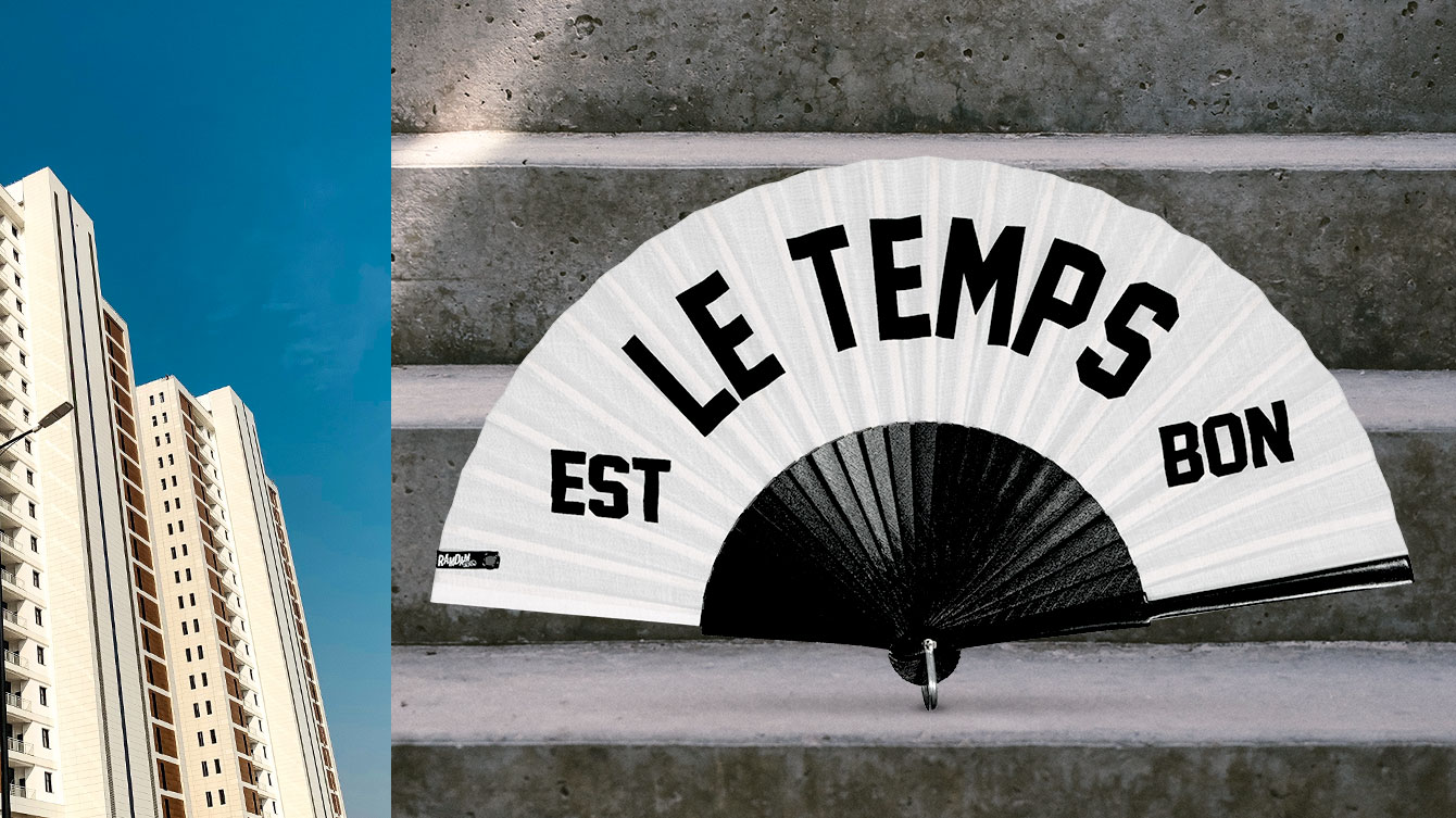 "Black and white hand fan with ""Le temps est bon"" text on concrete stairs."