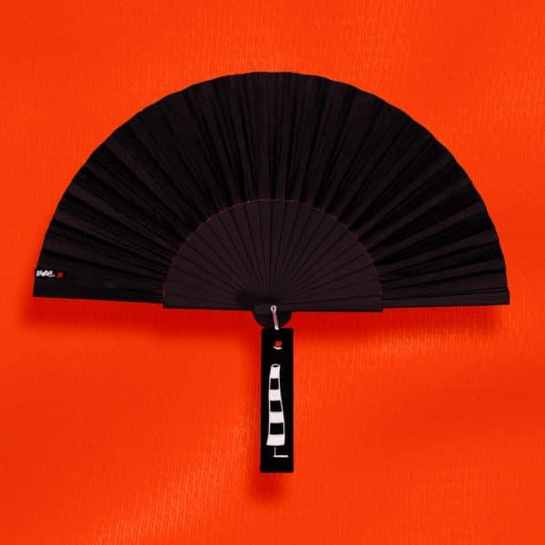 Éventail BLOW en tissu noir, monture en bois peint noir, étiquette brodée motif chambre à air noir et blanc.