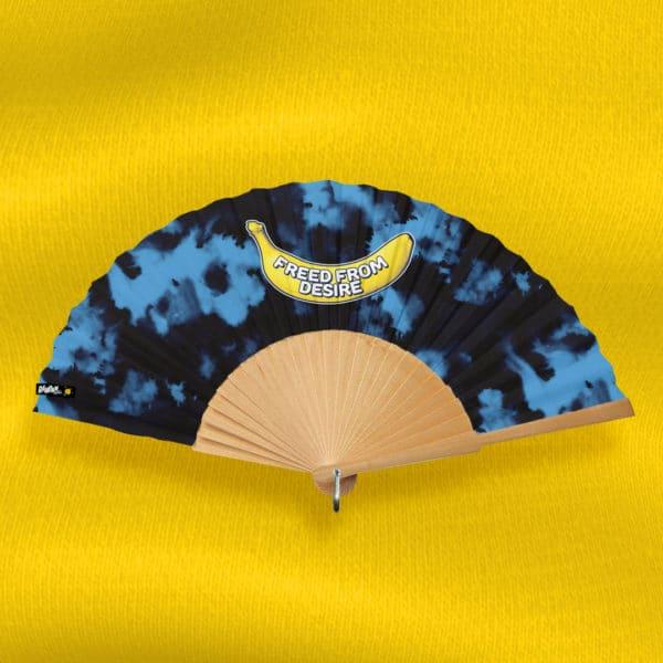 Éventail FREED FROM DESIRE en tissu imprimé, motif banane et texte sur fond tie-dye bleu et noir, monture en bois naturel poli à la main