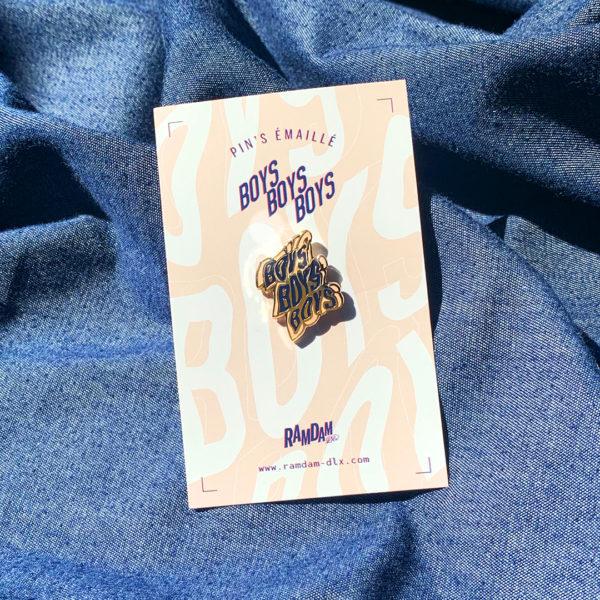 Pin's émaillé BOYS BOYS BOYS en zamak doré et émail 2 couleurs (bleu et rose pêche) sur cartonette imprimée.