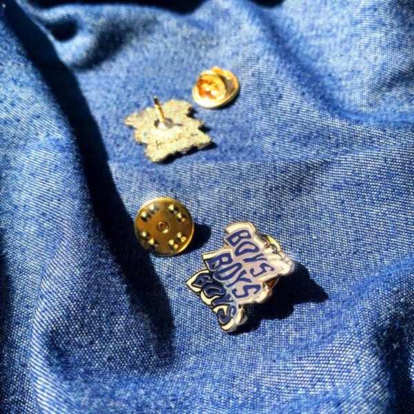 """Pin's émaillé BOYS BOYS BOYS en zamak doré et émail 2 couleurs (bleu et rose pêche), estampillé """"Ramdam Dlx"""" au dos. Agrafe papillon en métal doré."""