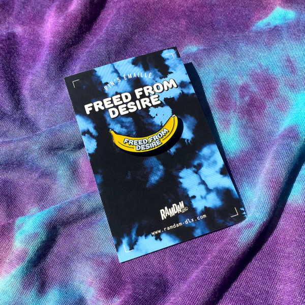 FREED FROM DESIRE enamel pin in navy blue plated zamak, 2 enamel colors (yellow and white) on printed backing card.