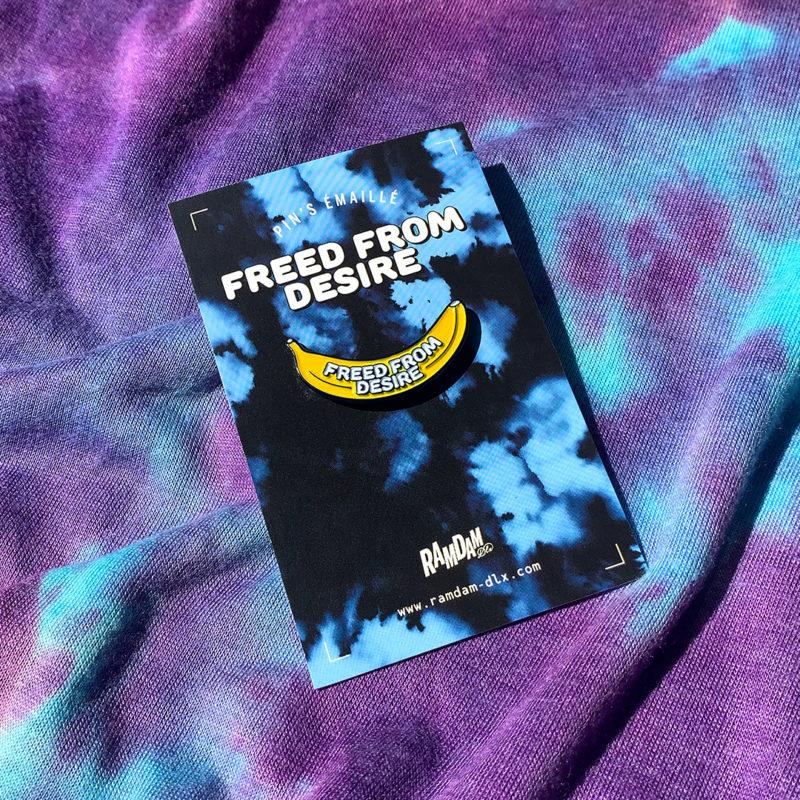 Pin's émaillé FREED FROM DESIRE en zamak plaqué bleu marine et émail 2 couleurs (jaune et blanc) sur cartonette imprimée.