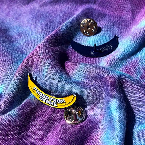 """Pin's émaillé FREED FROM DESIRE en zamak plaqué bleu marine et émail 2 couleurs (jaune et blanc), estampillé """"Ramdam Dlx"""" au dos. Agrafe papillon en métal argenté."""