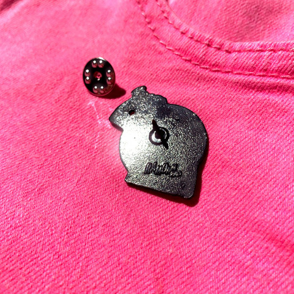 """Pin's NO DRAMA en zamak plaqué noir, estampillé """"Ramdam Dlx"""" au dos. Agrafe papillon en métal argenté."""