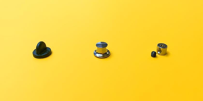 Trois types d'attaches pour pin's en option : attache en caoutchouc ; attache premium à ressort ; attache de sécurité à verrou