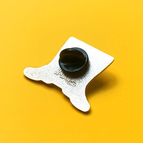 Exemple d'attache en caoutchouc noir fixée au dos d'un pin's émaillé