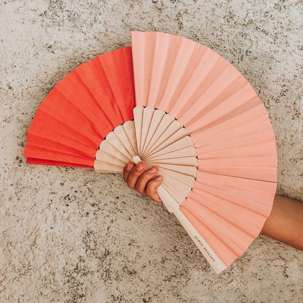 Two Spanish fans in organic cotton from the Arena Stories brand, brick and light pink colors, held by one hand in front of a plastered wall