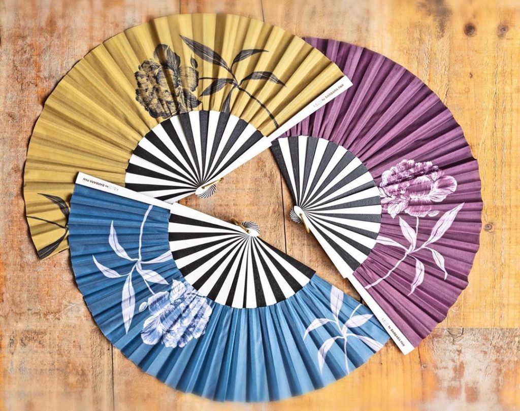 Three Spanish hand fans from Kausi by Barbara Pan, black and white wooden frame, peony design on mustard, eggplant and blue backgrounds, placed on a wooden floor