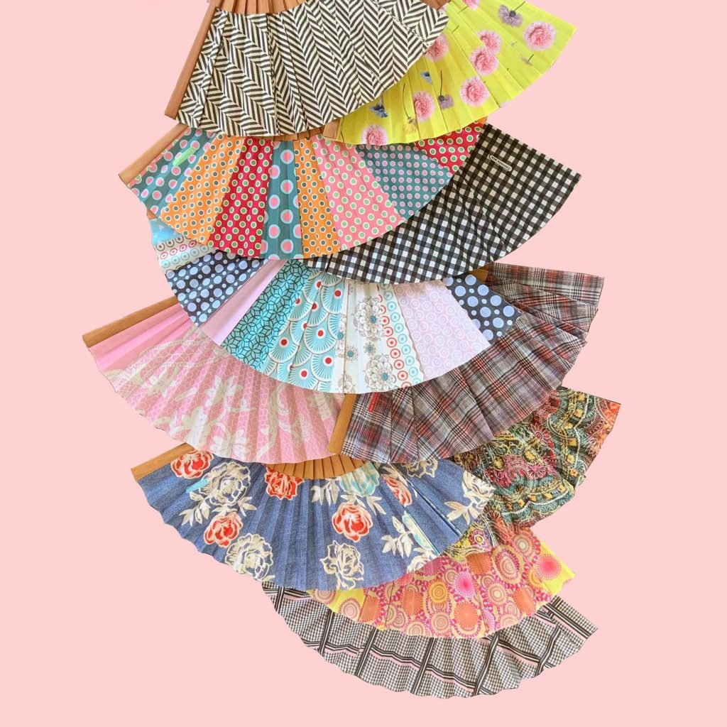 Graphic composition of multiple Spanish fans, fabrics with various patterns, patchwork, on a pale pink background