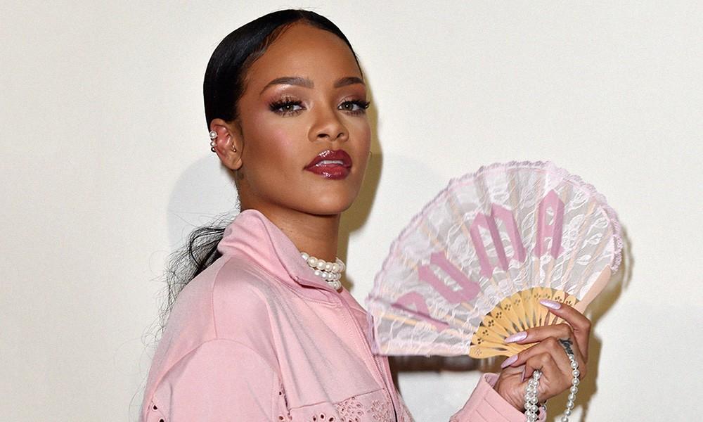 """Éventail en dentelle rose pastel avec sérigraphie """"PUMA"""" en lettres gothiques, monture en bambou, lanière en nylon rose de Fenty X Puma (by Rihanna)"""