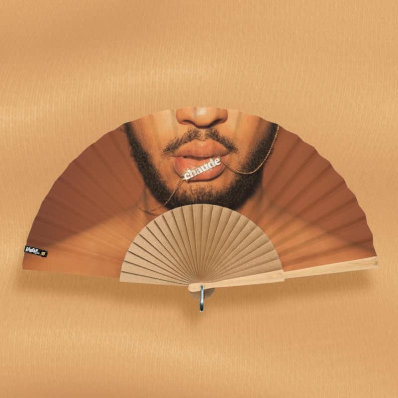 """Éventail CHAUDE (série """"Bisou Bijou"""") en tissu imprimé, motif photographie, pendentif """"Chaude"""" doré sur une bouche d'homme noir barbu, monture en bois naturel poli à la main"""